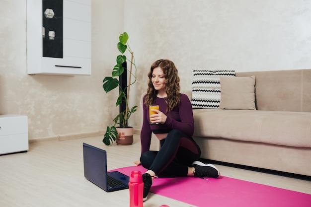 Kobieta siedzi na różowej macie do jogi z laptopem i pije świeży sok w domu