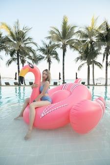 Kobieta siedzi na różowych flamingach nadmuchiwany materac w basenie w pobliżu plaży.