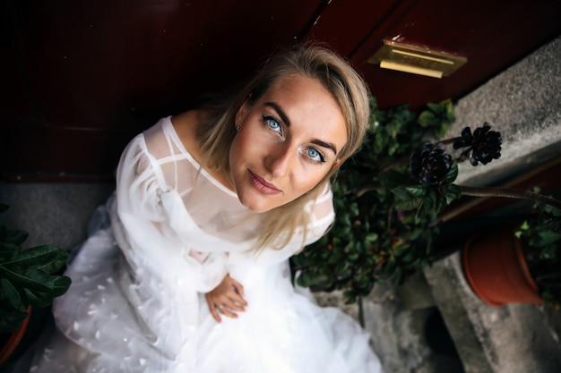 Kobieta siedzi na schodach domu i spogląda w górę