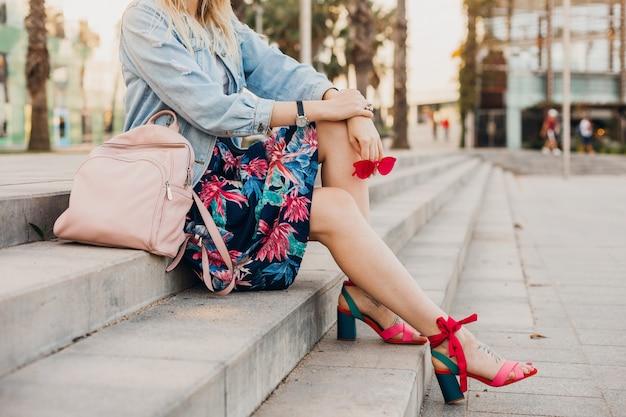 Kobieta siedzi na schodach na ulicy miasta w drukowanej spódnicy ze skórzanym plecakiem trzymając okulary przeciwsłoneczne