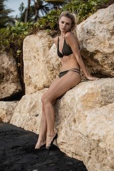 Kobieta siedzi na skałach w ciągu dnia