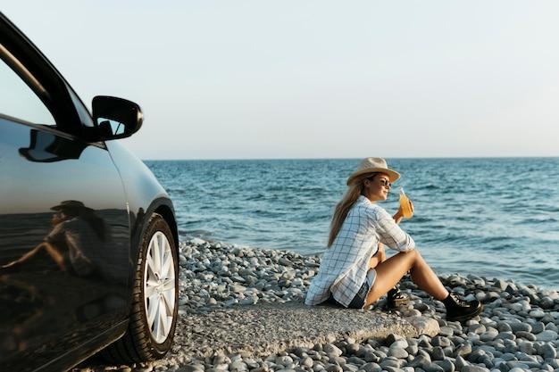 Kobieta siedzi na skałach z sokiem patrząc na morze w pobliżu samochodu