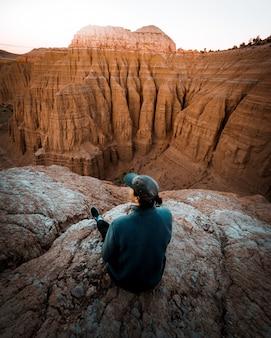 Kobieta siedzi na skraju skały z niesamowitymi wysokimi górami skalistymi