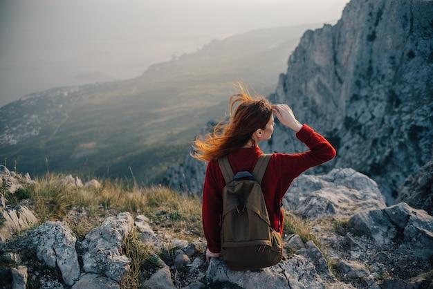 Kobieta siedzi na skraju urwiska