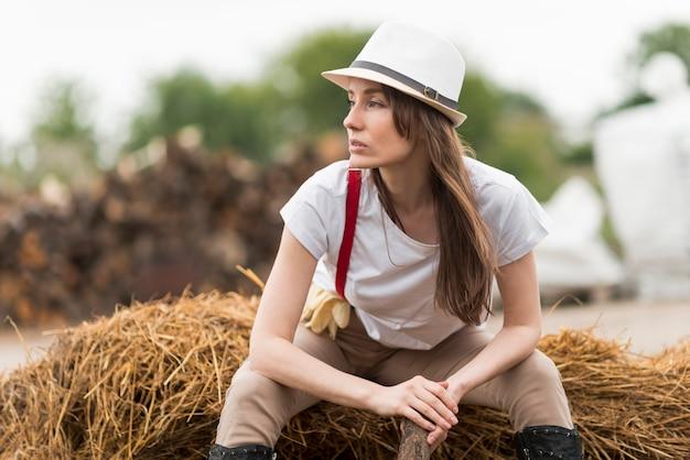 Kobieta siedzi na słomie w gospodarstwie