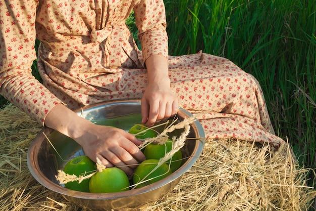 Kobieta siedzi na stogu siana z jabłkami na zielonej łące