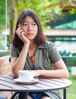 Kobieta siedzi na tarasie kawiarni