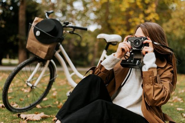Kobieta siedzi na trawie i robi zdjęcia
