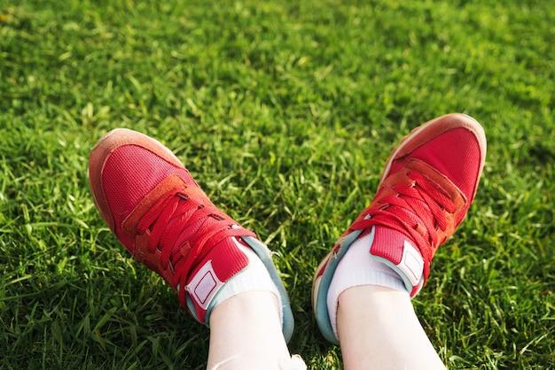 Kobieta siedzi na trawie kobieta nogi w czerwonych trampkach na zielonej trawie