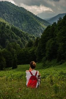 Kobieta siedzi na trawie, patrząc na wzgórza pokryte zielenią