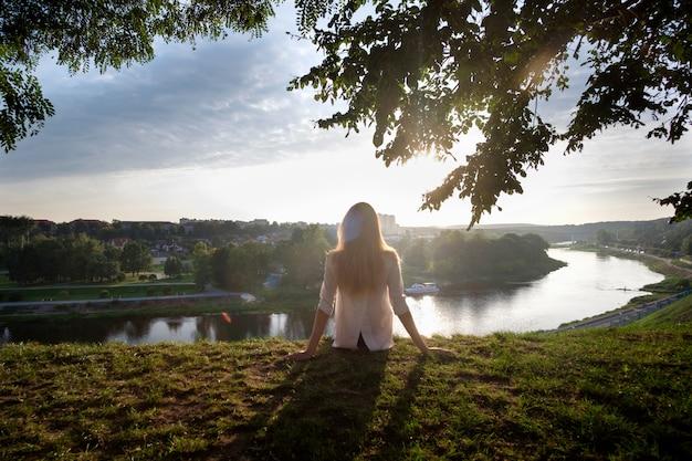 Kobieta siedzi na trawie, relaksując się i podziwiając widok na rzekę