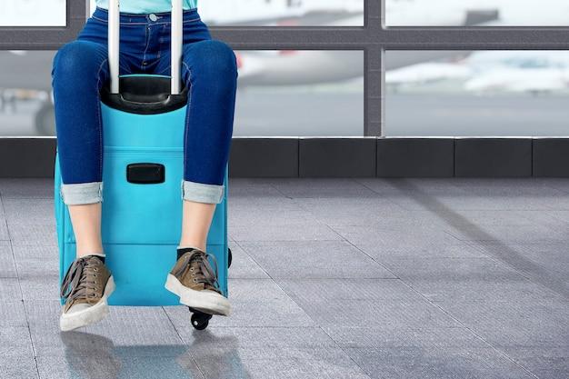 Kobieta siedzi na walizce na terminalu lotniska