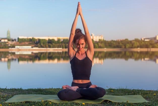 Kobieta siedzi na zewnątrz medytacji w pozycji jogi w pobliżu rzeki.