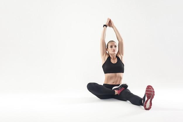 Kobieta siedzi na ziemi i robi jogę.studio shor