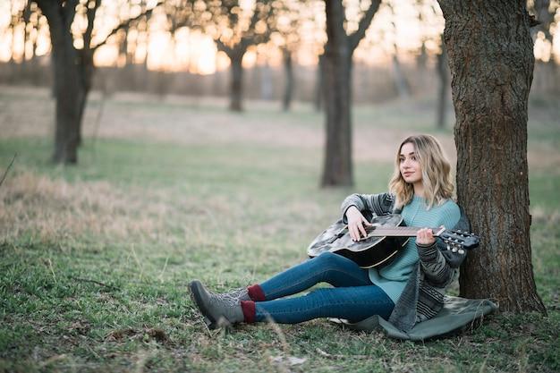 Kobieta siedzi na ziemi z gitarą