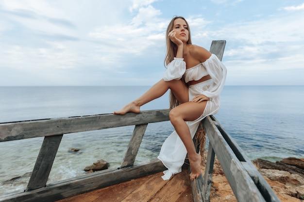 Kobieta siedzi na zniszczonym statku na brzegu