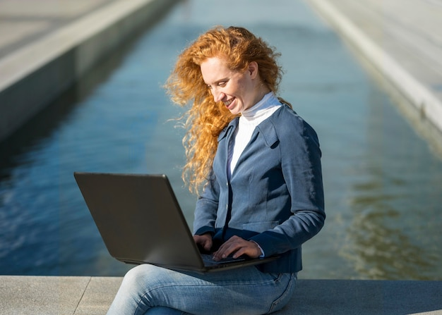 Kobieta siedzi obok rzeki i pracuje