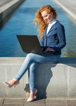 Kobieta siedzi obok rzeki i pracy długi widok