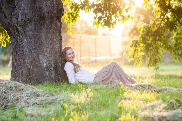 Kobieta siedzi pod drzewem i ogląda zachód słońca