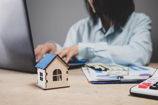 Kobieta siedzi przed domem. kupno domu