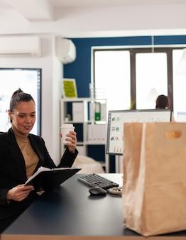 Kobieta siedzi przy biurku w biurze firmy, czytając statystyki finansowe w schowku, przed delektowaniem się smacznym, pysznym jedzeniem na wynos w papierowej torbie