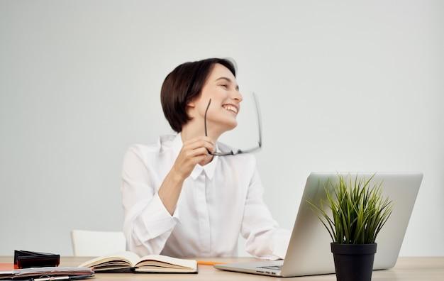 Kobieta siedzi przy biurku w okularach przed laptopem kierownik biura kierownika