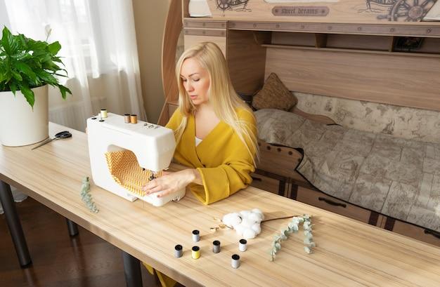 Kobieta siedzi przy maszynie do szycia