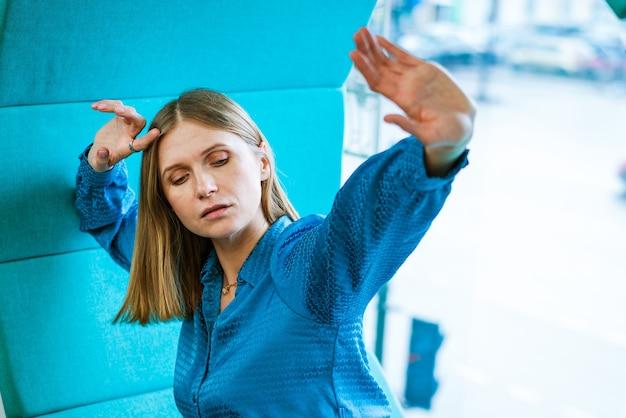 """Kobieta siedzi przy oknie i pokazuje gestem ręki """"nie"""" i """"opór"""" kaukaska dziewczyna w niebieskiej sukience..."""