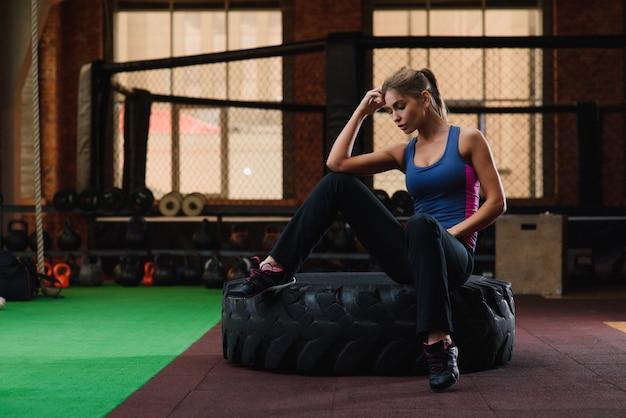 Kobieta siedzi przy oponą w gym