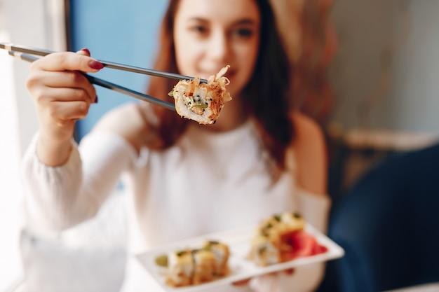 Kobieta siedzi przy stole i jedzenie sushi w kawiarni