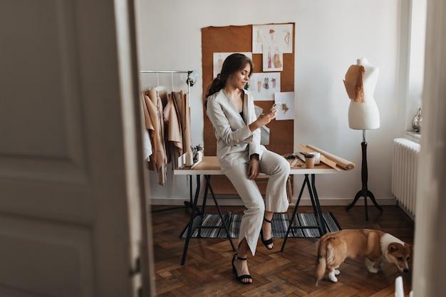 Kobieta siedzi przy stole i robi zdjęcia swojemu psu