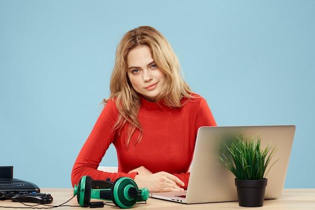 Kobieta siedzi przy stole przed kontrolerem słuchawek laptopa grając online niebieski styl życia