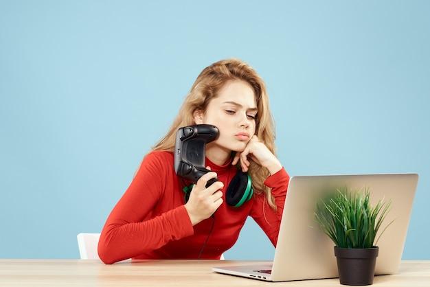 Kobieta siedzi przy stole przed kontrolerem słuchawki laptopa, grając online