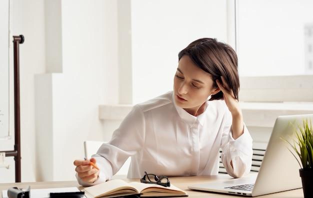 Kobieta siedzi przy stole roboczym przed kierownikiem biura finansów laptopa