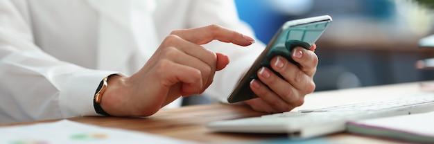 Kobieta siedzi przy stole w biurze z telefonem komórkowym w dłoniach zbliżenie
