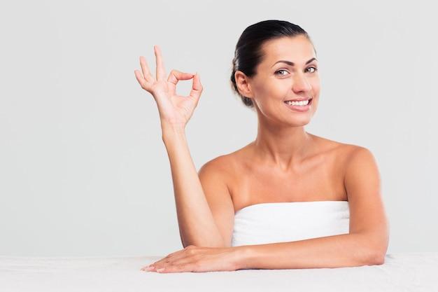 Kobieta siedzi przy stole w ręcznik i pokazuje znak ok