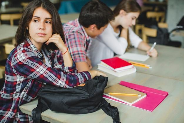 Kobieta siedzi przy stole z innymi studentami