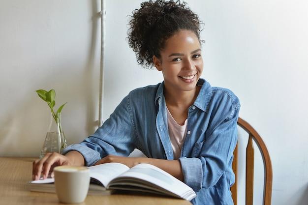 Kobieta siedzi przy stole z książką