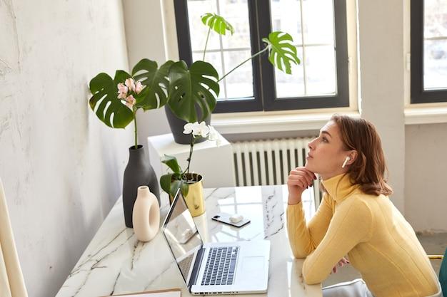 Kobieta siedzi przy stole z laptopem i słucha muzyki