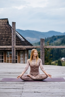Kobieta siedzi rano w pozycji lotosu na świeżym powietrzu.