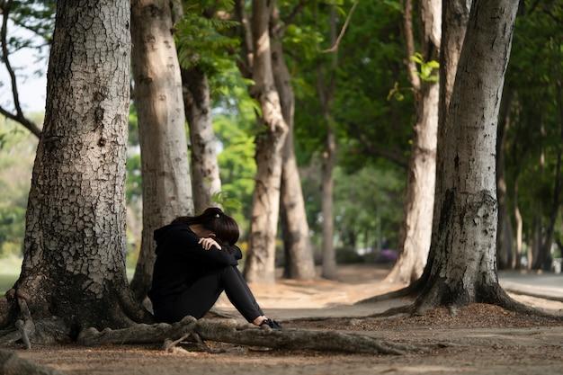 Kobieta siedzi samotna i smutna z twarzą między ramionami na podłodze parku