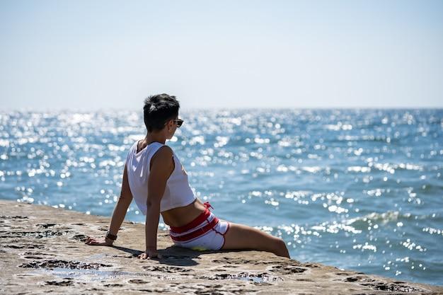 Kobieta siedzi samotnie na molo w krótkich spodenkach i podkoszulku z butami. widok z tyłu. letnie morze