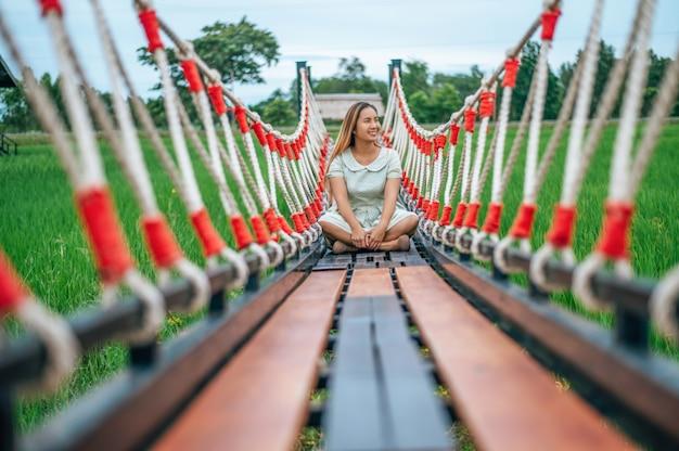 Kobieta siedzi szczęśliwie na drewnianym moscie