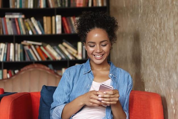 Kobieta siedzi w bibliotece na kanapie