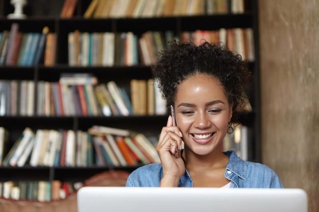 Kobieta siedzi w bibliotece z laptopem