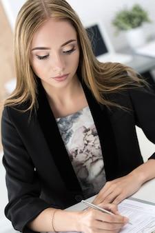 Kobieta siedzi w biurze i podpisuje niektóre dokumenty. życie biurowe.