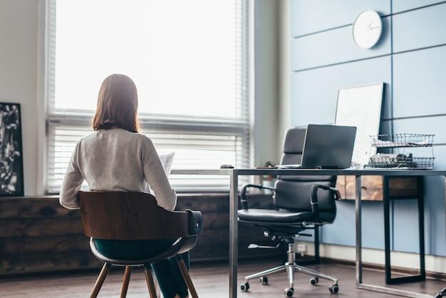 Kobieta siedzi w biurze kierownika czekając na spotkanie.