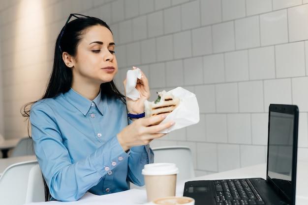 Kobieta siedzi w biurze przy stole, pije kawę i je kanapkę