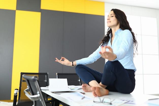 Kobieta siedzi w biurze w pozycji lotosu i medytuje.