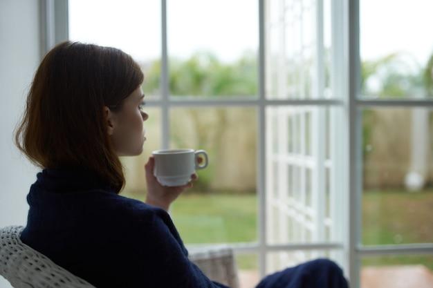 Kobieta siedzi w domu i wygląda przez okno przy filiżance kawy